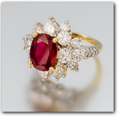 Pala International - Thai ruby surrounded by diamonds in a gold ring setting.
